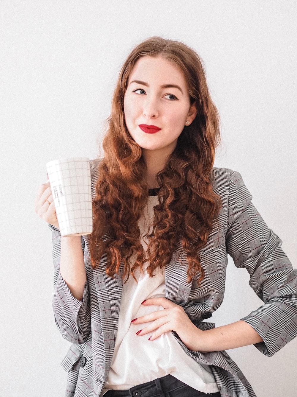 woman in gray cardigan holding white ceramic mug