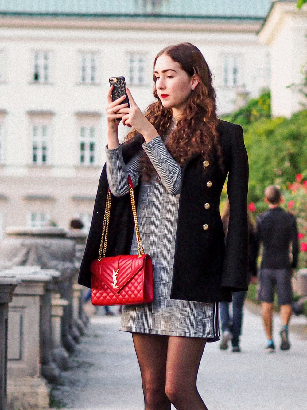 woman in black coat holding red leather handbag