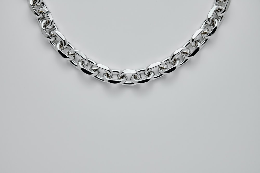 silver chain link bracelet on white surface