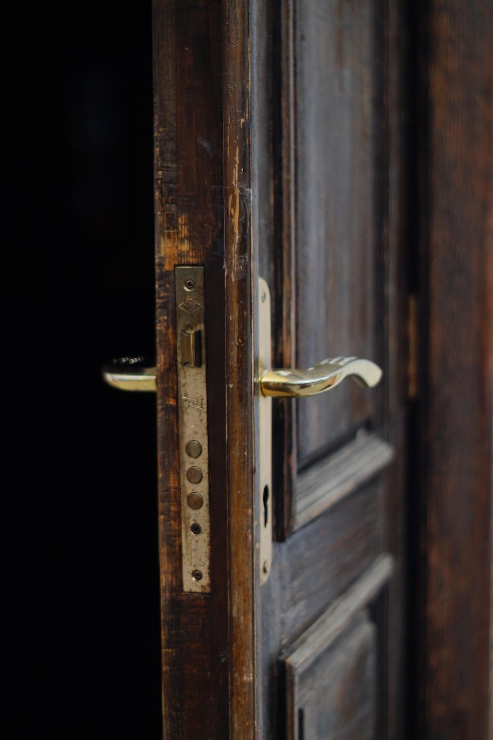 gold door lever on brown wooden door