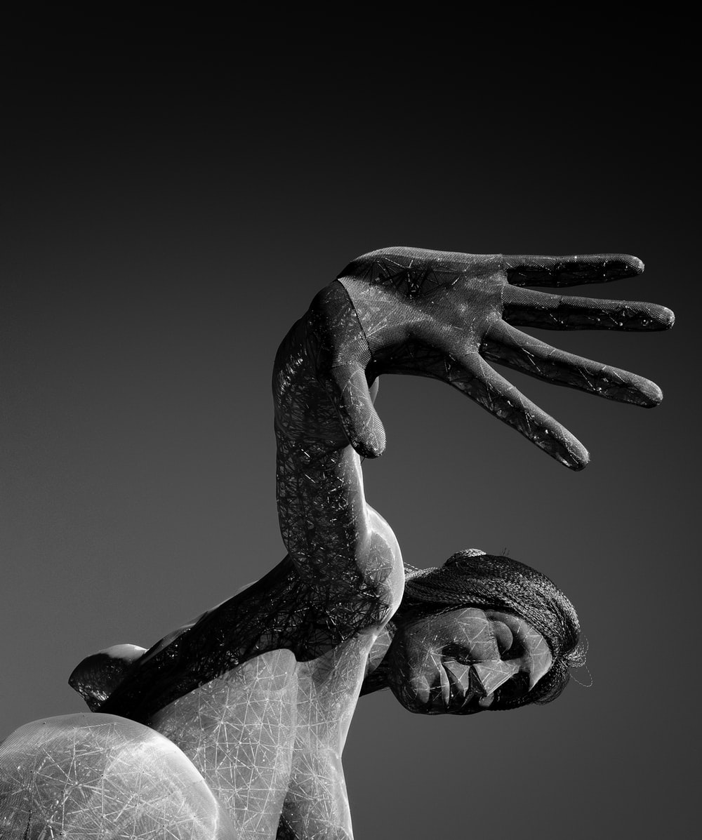 grayscale photo of man holding womans hand statue