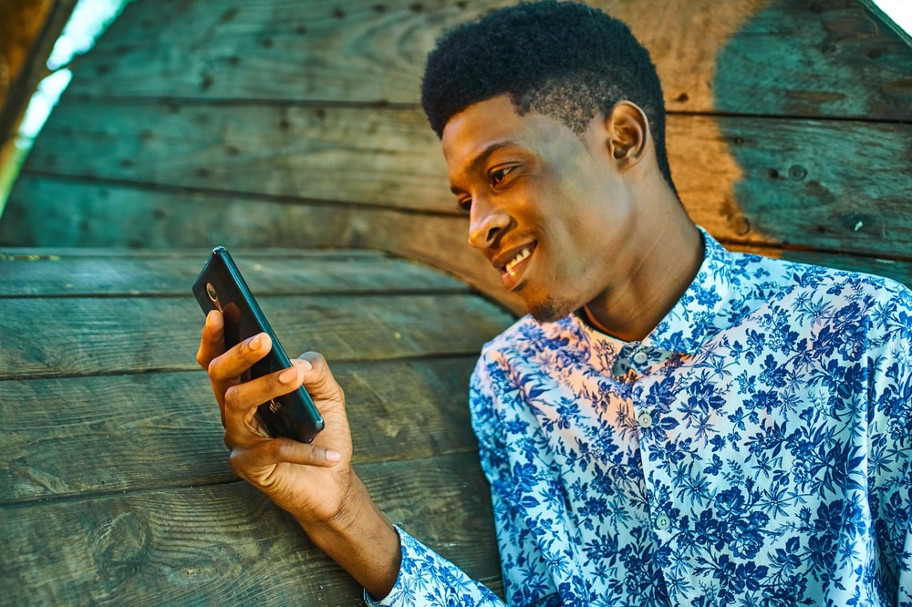 man in blue and white floral button up shirt holding black smartphone