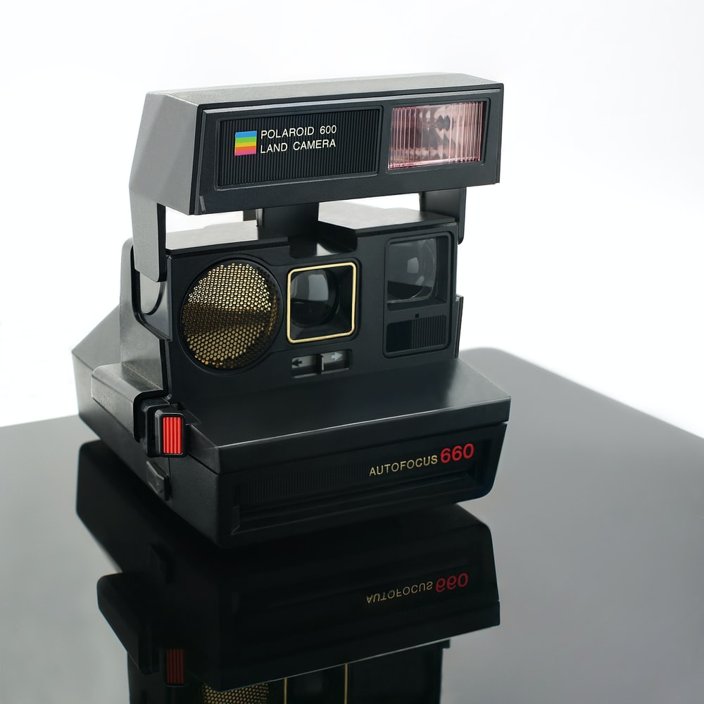 black polaroid instant camera on white surface