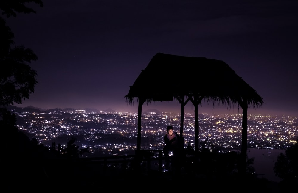 silhouette of 2 people sitting on beach shore during night time