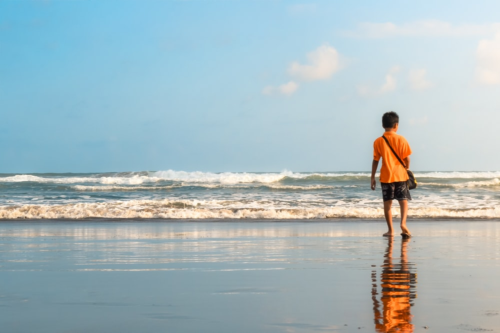 man in orange shirt and black shorts walking on seashore during daytime