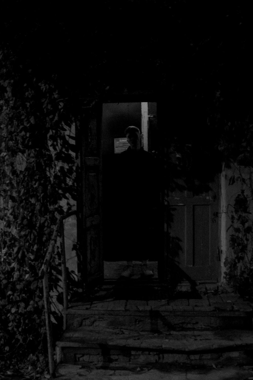 man in black jacket standing in front of mirror