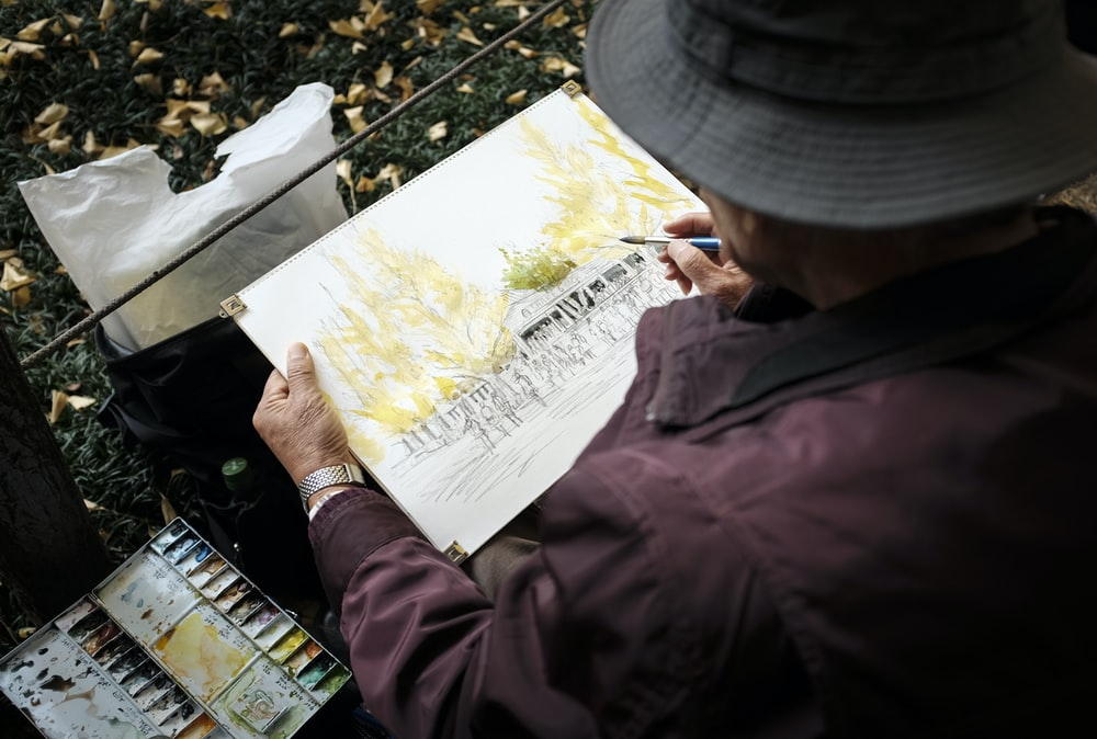 man in red jacket and gray cap holding white printer paper