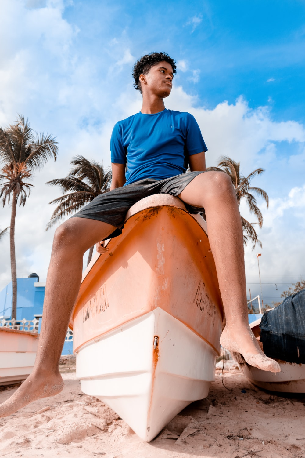 man in blue crew neck t-shirt sitting on orange and white boat during daytime