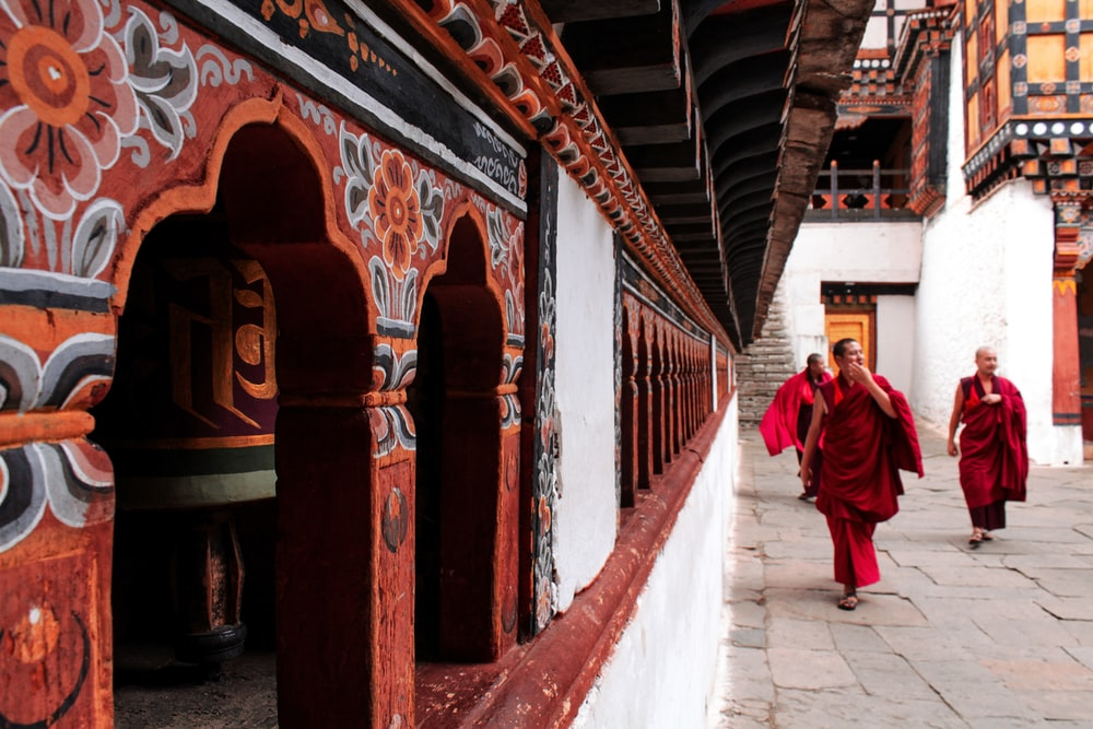 man in red robe walking on hallway
