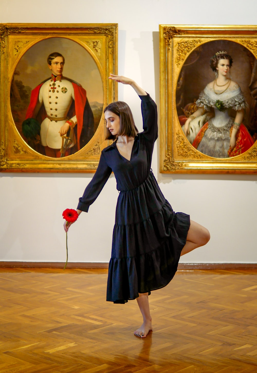 woman in black dress holding red heart balloon