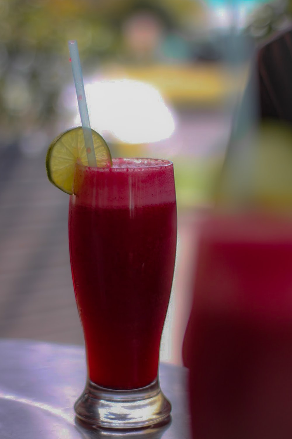 red liquid in clear drinking glass with sliced lemon
