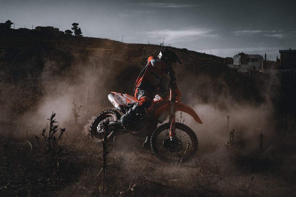 man riding red and black motocross dirt bike