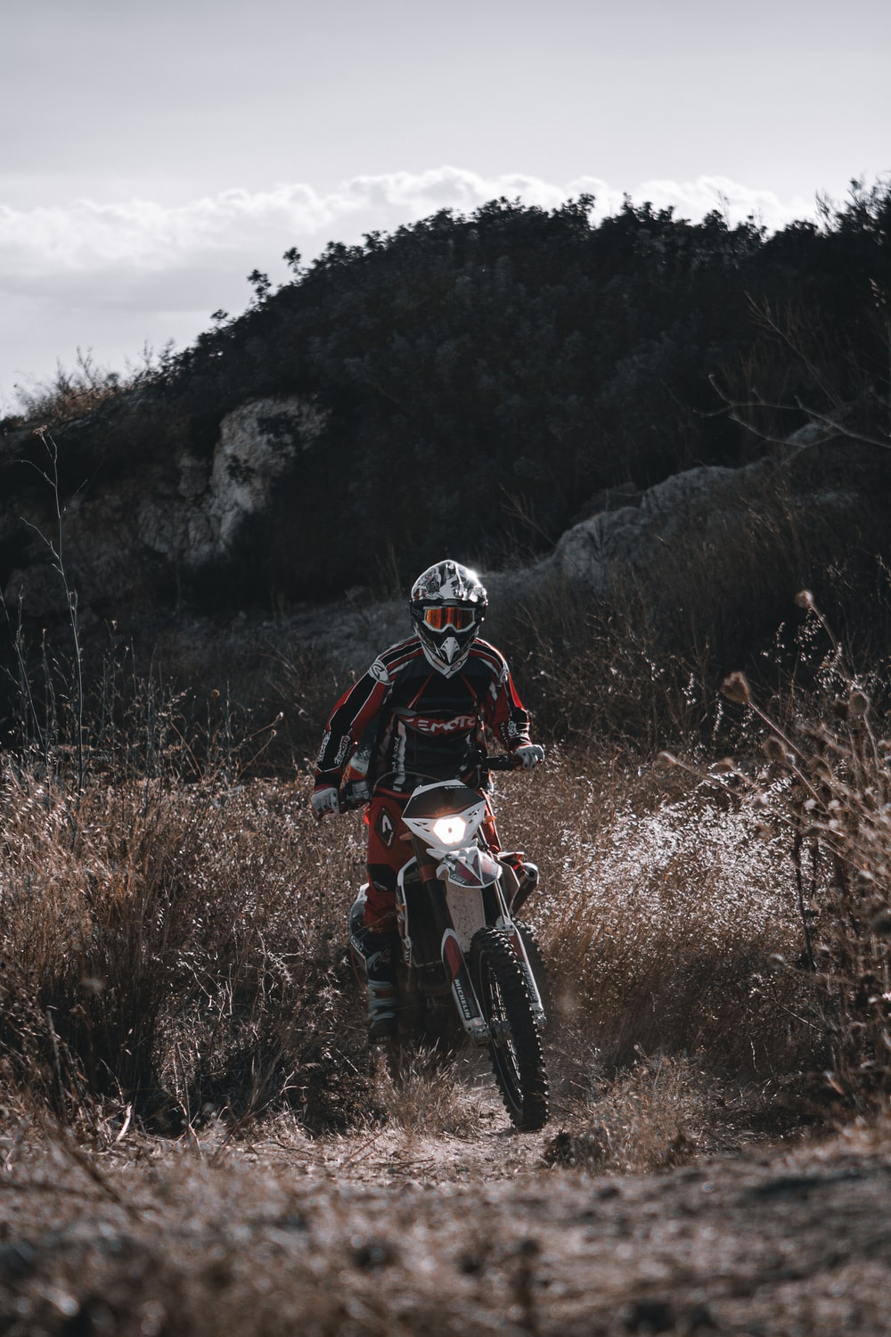 man in red and black motorcycle suit riding on red and white motocross dirt bike
