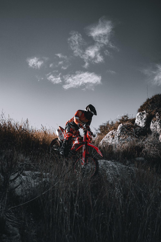 man in orange jacket riding on red dirt bike