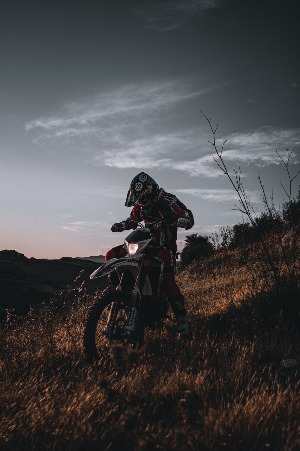 man in black and red motorcycle suit riding motocross dirt bike on brown grass field during