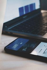 black android smartphone beside black laptop computer