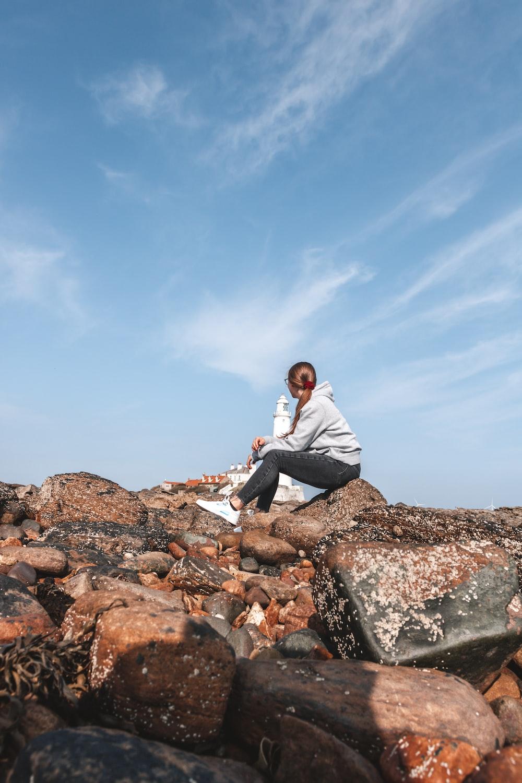 man in white dress shirt sitting on rock during daytime