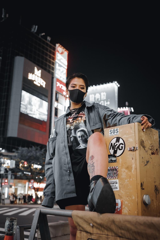man in black leather jacket wearing black sunglasses standing beside brown cardboard box during daytime