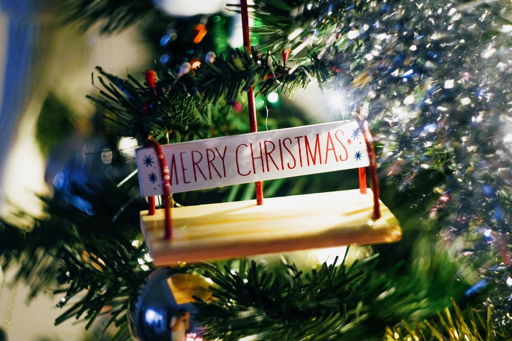 brown wooden hanging signage on christmas tree