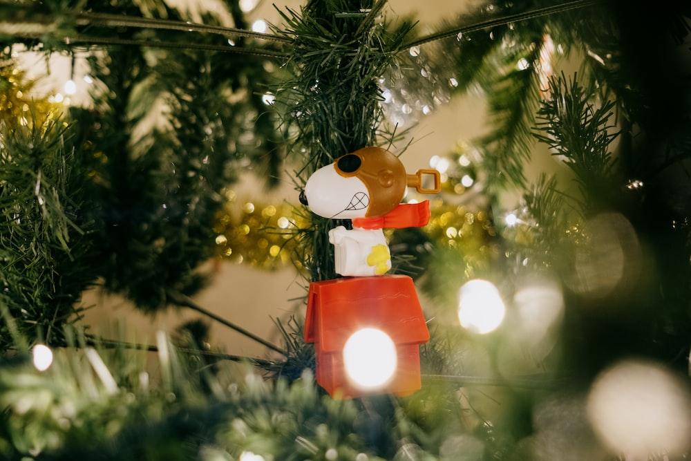 brown bear plush toy hanging on green christmas tree