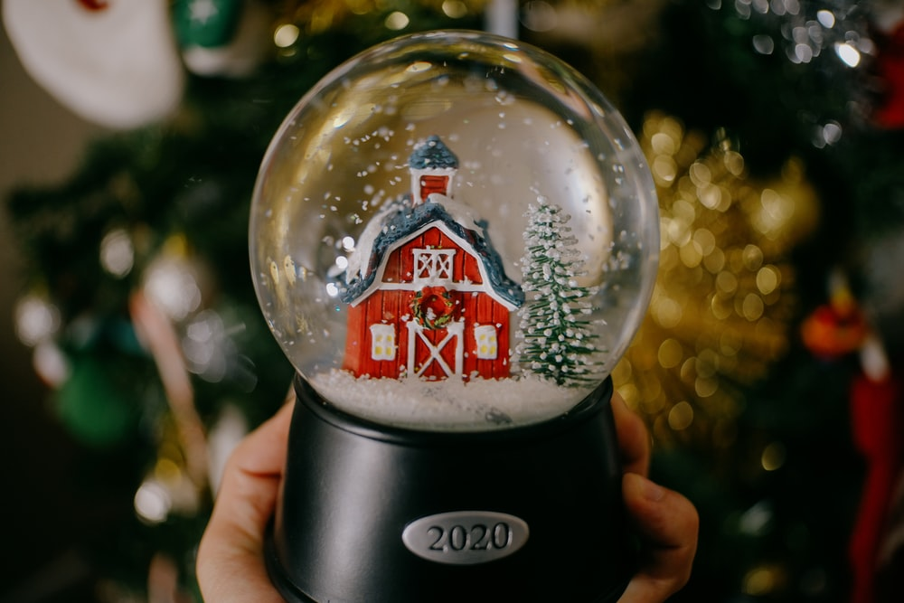 person holding black and red snow globe