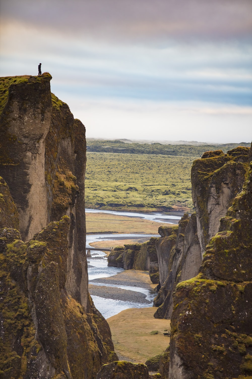 person standing on rock formation near body of water during daytime