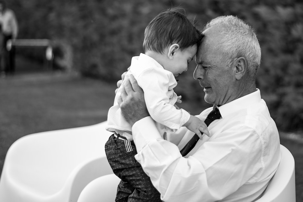 man in white dress shirt carrying baby in black and white long sleeve shirt