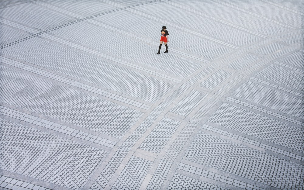 person in red jacket and black pants walking on white snow field during daytime