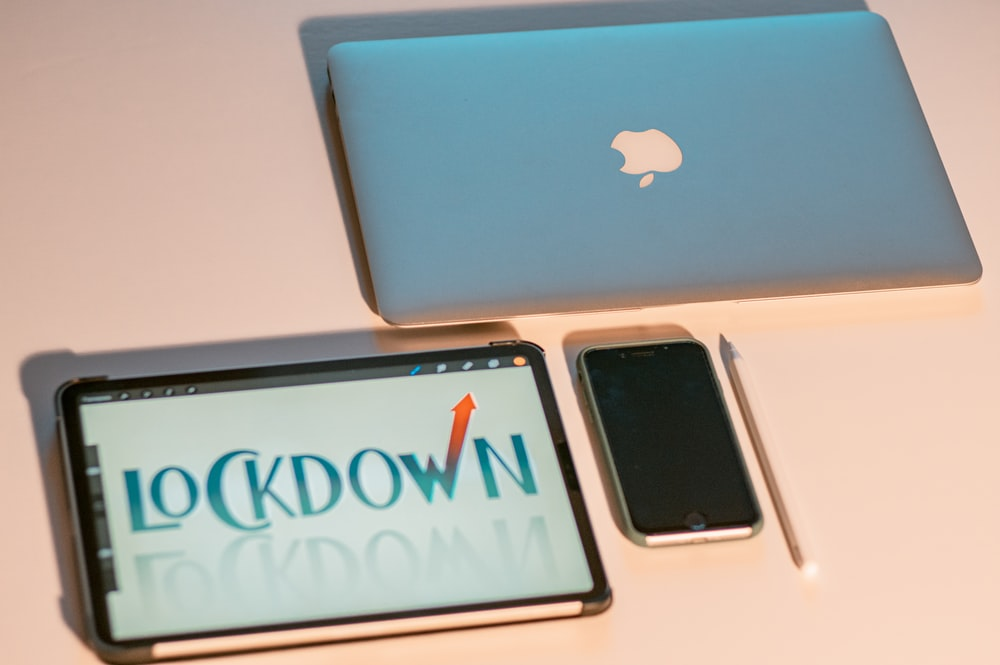 silver iphone 6 beside silver macbook
