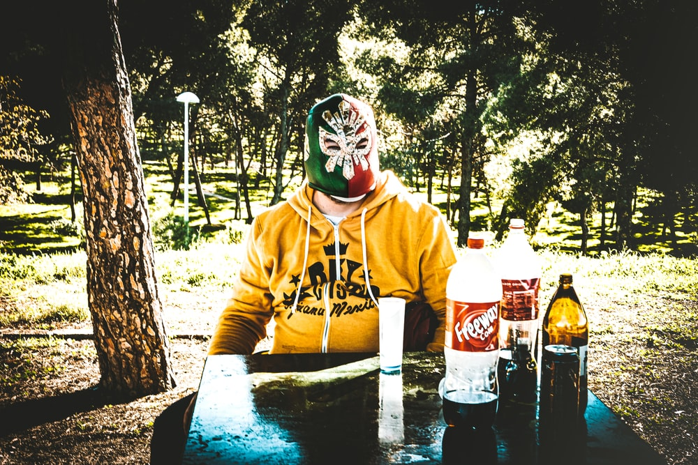 person in yellow hoodie wearing mask and mask holding coca cola bottle