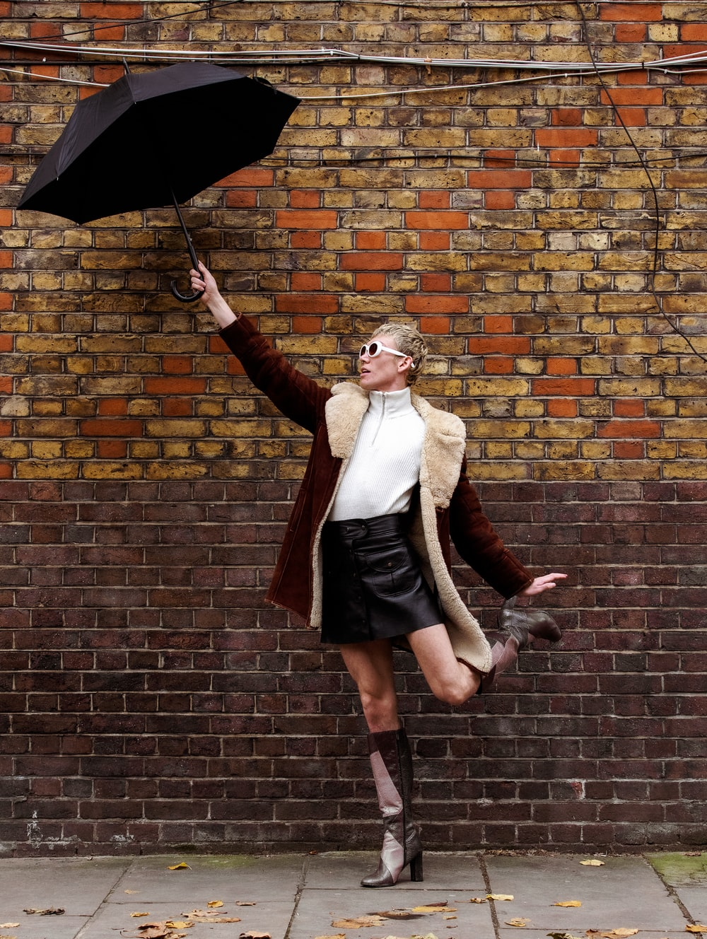 woman in black skirt holding umbrella standing beside brick wall