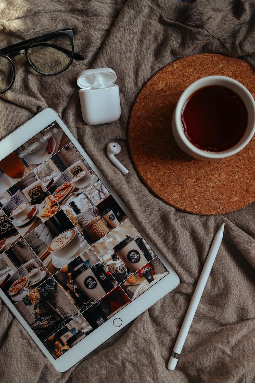 white ipad beside white ceramic mug on brown wooden table