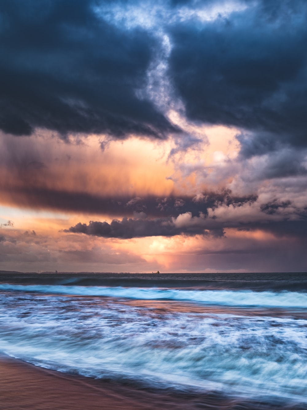 ocean waves under cloudy sky during daytime
