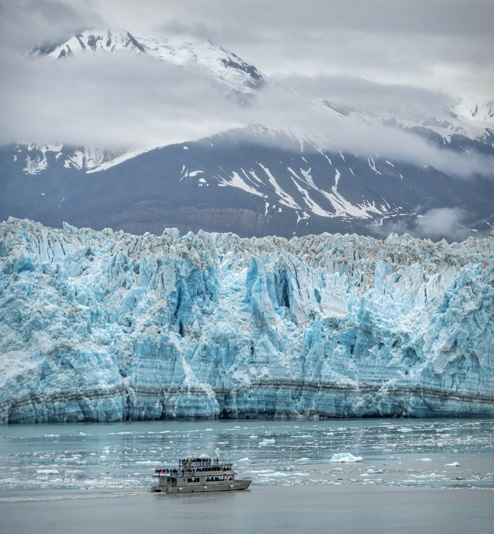 white boat on body of water near snow covered mountain during daytime
