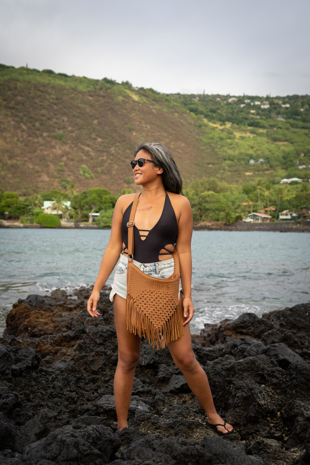 woman in black and brown polka dot bikini standing on rocky shore during daytime