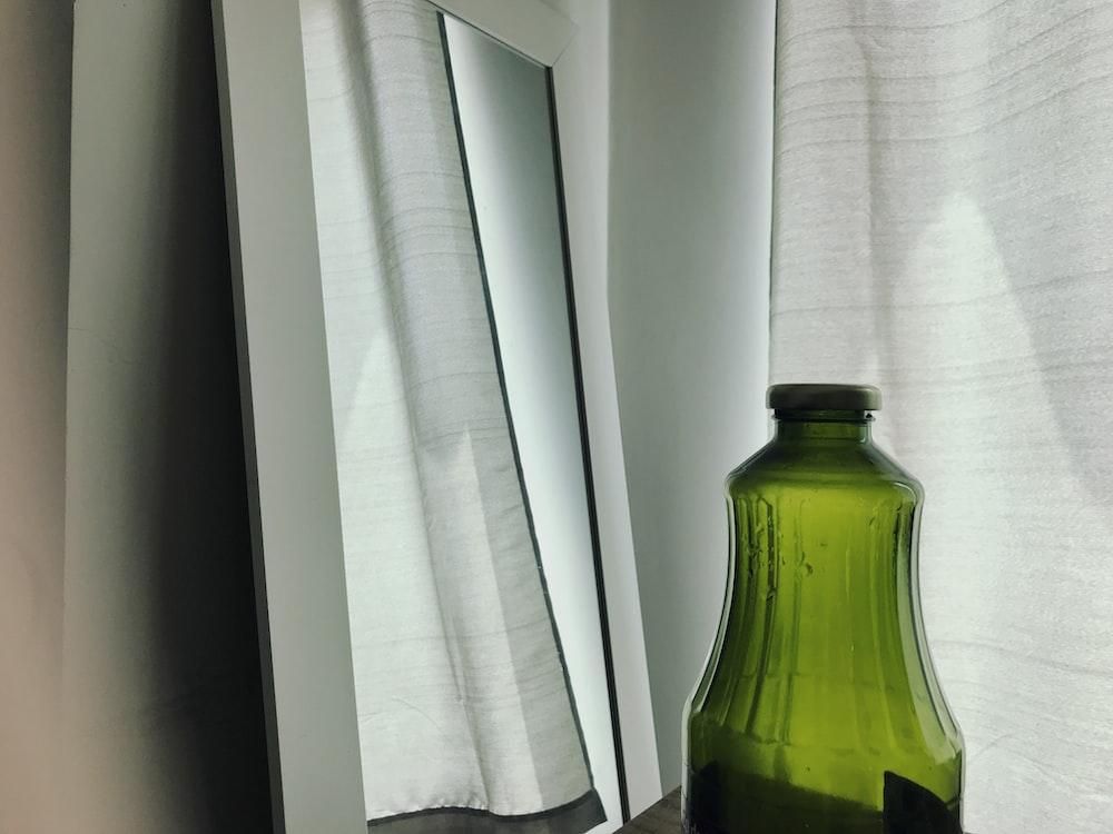 green glass bottle near white window curtain