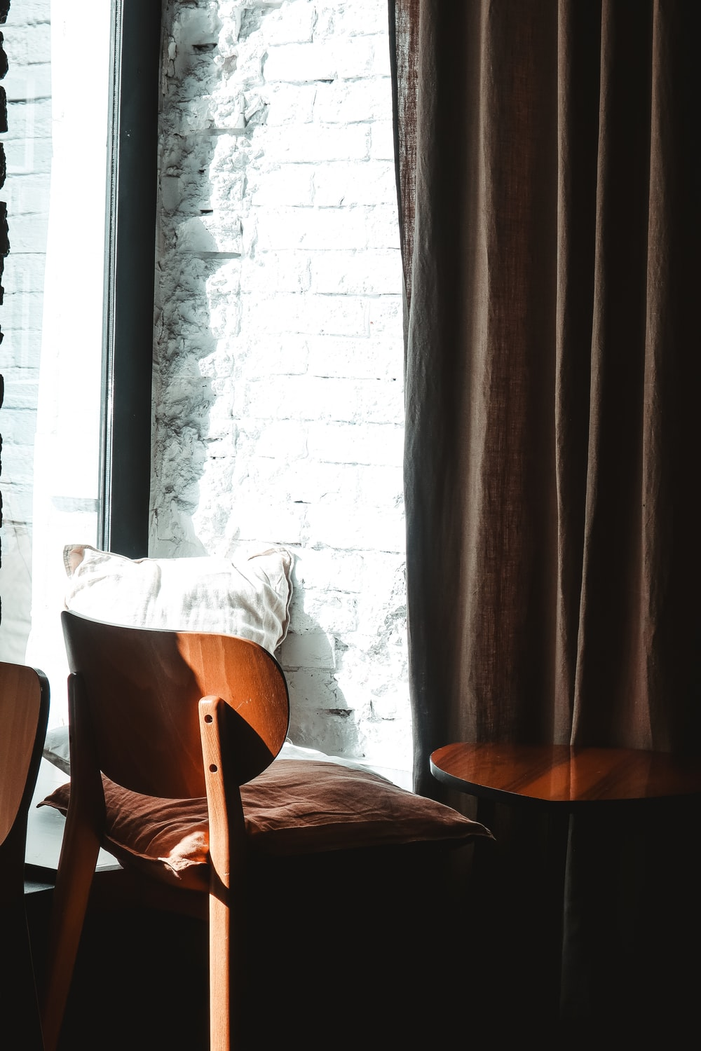 brown wooden table near brown window curtain