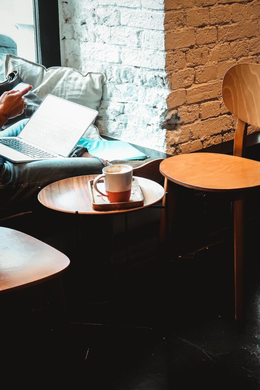 white ceramic mug on brown wooden round table