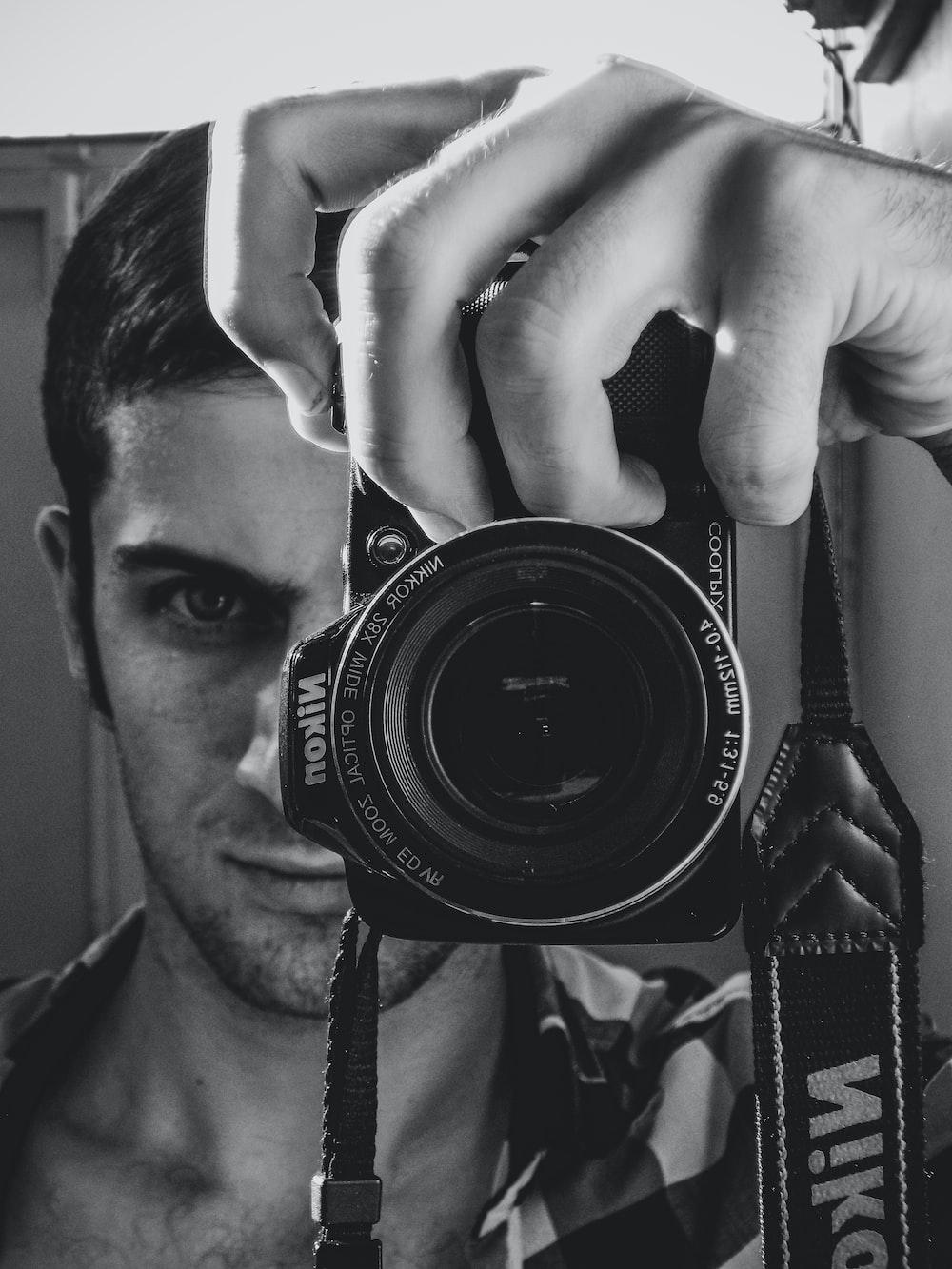 grayscale photo of man holding nikon dslr camera