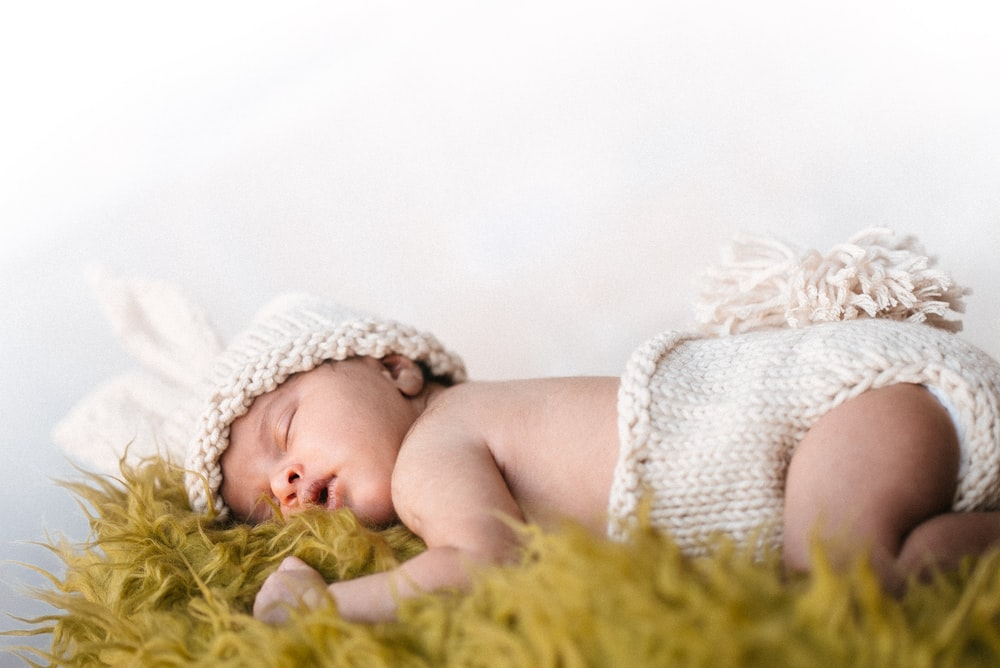 baby in white knit cap lying on green textile