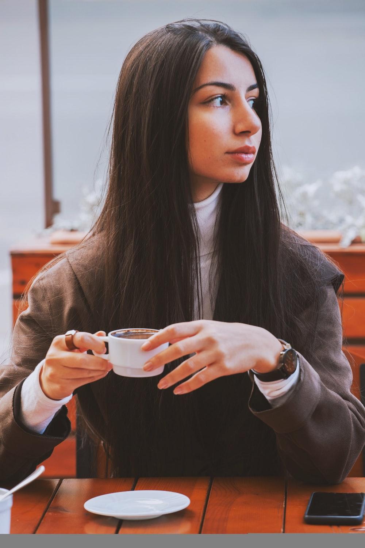 woman in brown coat holding white ceramic mug