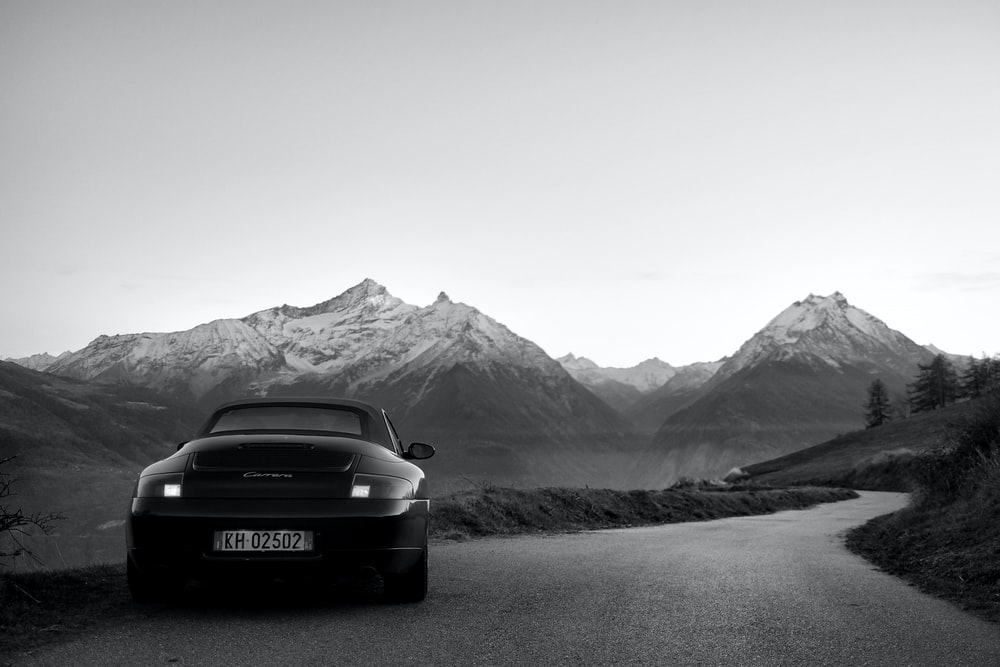 black car on road near snow covered mountain during daytime
