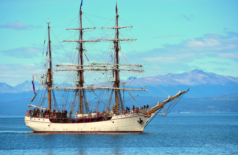 white and brown ship on sea under blue sky during daytime