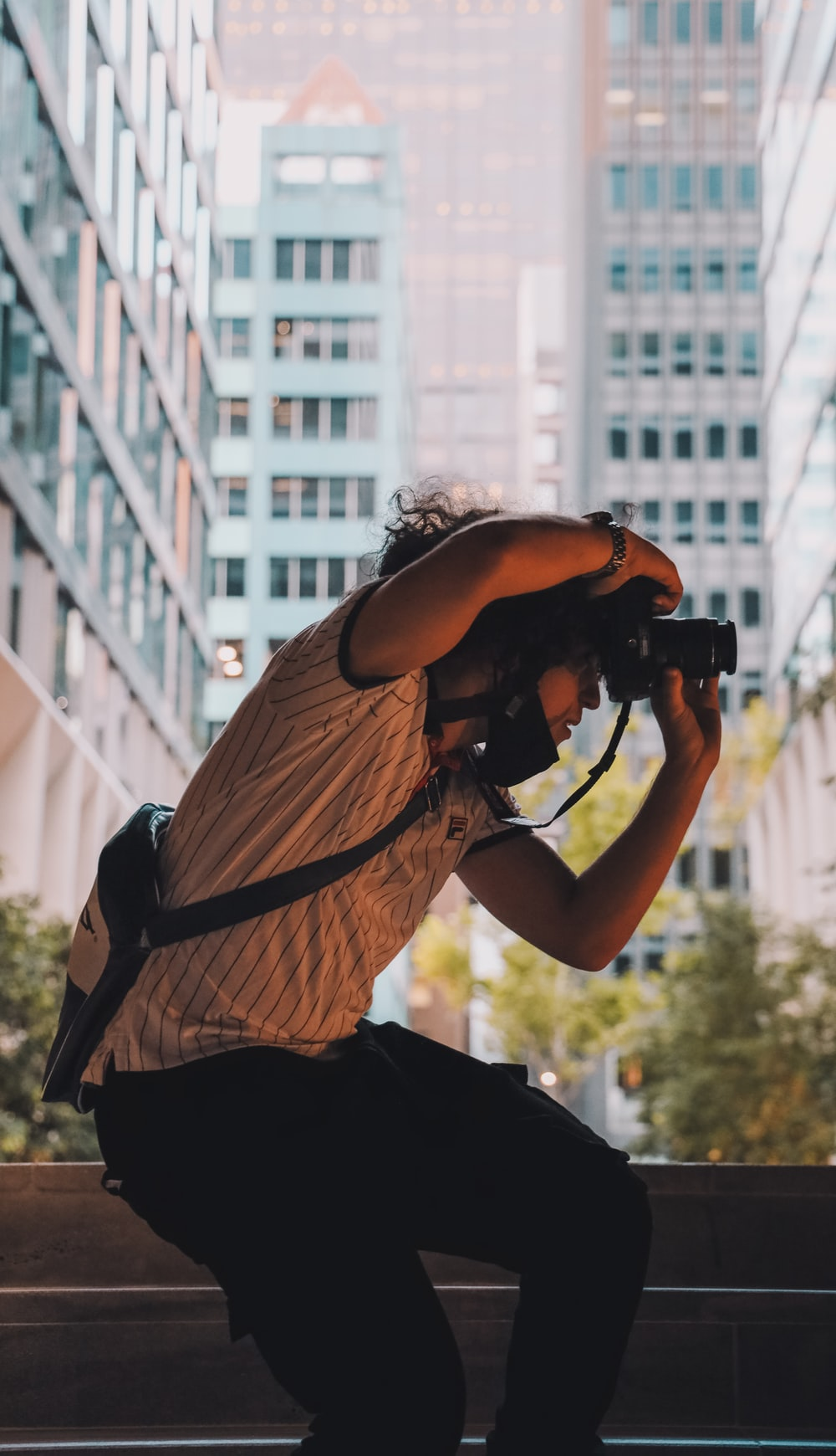 man in brown t-shirt and black pants holding black dslr camera