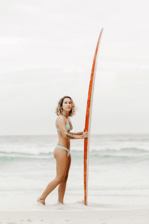 woman in pink bikini standing on beach during daytime