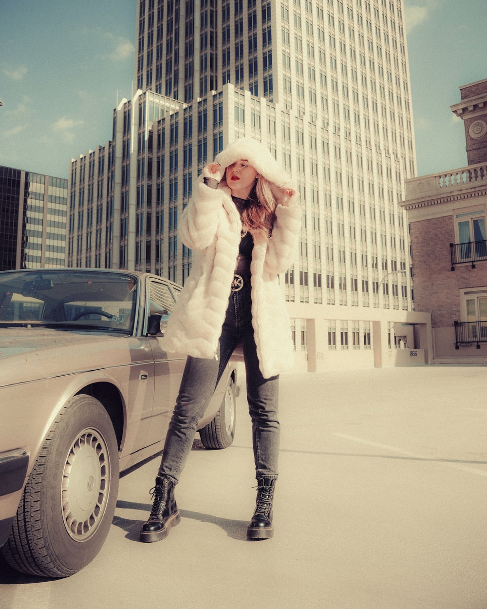 woman in white coat standing beside black car during daytime
