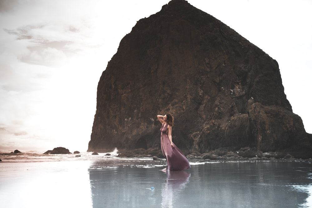 woman in green dress standing on rock formation near body of water during daytime
