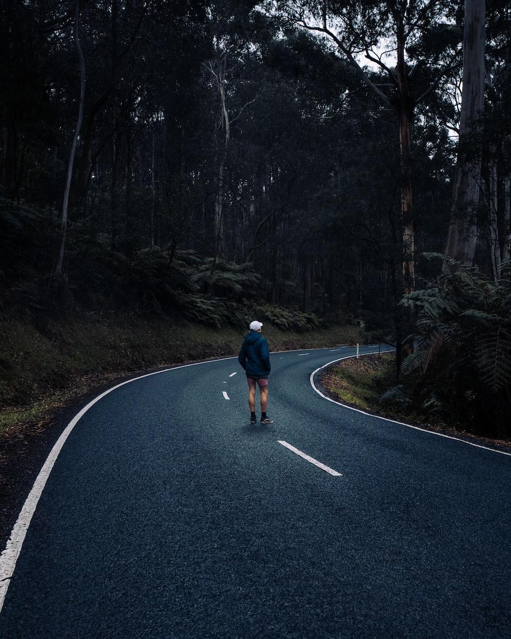 man in black jacket and blue denim jeans walking on road during daytime