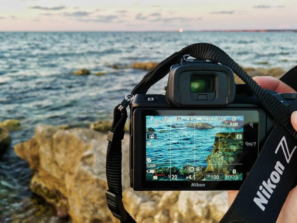 black samsung dslr camera taking photo of sea waves crashing on shore during daytime