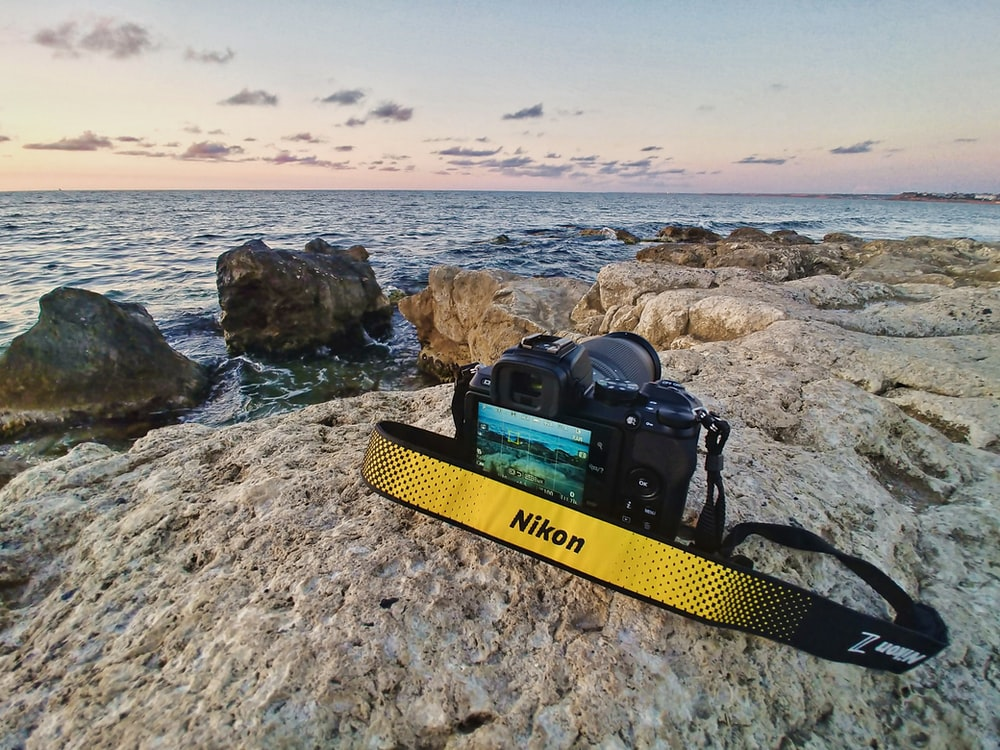 yellow and black bag on rocky shore during daytime